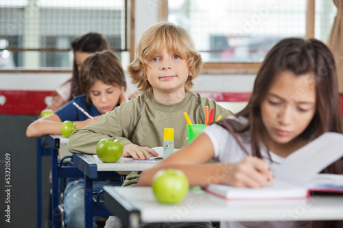 Schoolboy Sitting At Desk With Classmates In A Row