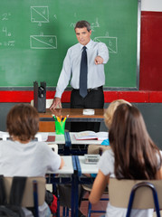 Teacher Pointing At Students In Classroom