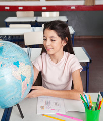 Schoolgirl Searching Places On Globe At Desk
