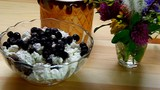 Blueberries stirred with a spoon with cottage cheese