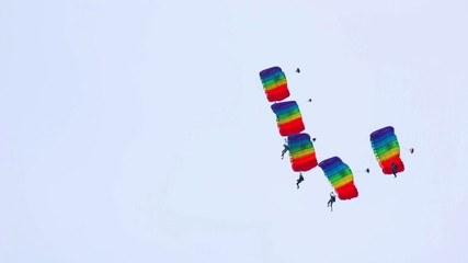Group of paragliders performing aerobatics.