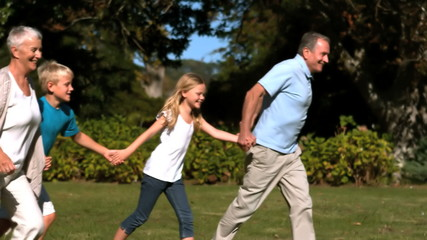Grandchildren and grandparents running hand in hand in a park