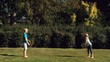 Happy brother throwing a football to a sister in a park