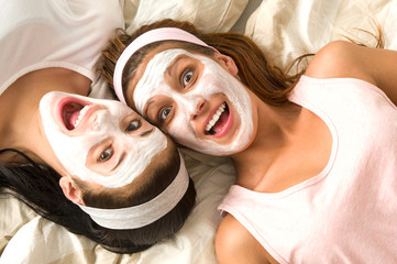 Crazy girls with facial mask lying bed