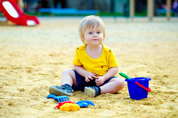 Cute kid playing with his toys in the sandbox