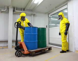 Workers in protective uniforms  wh barrels of toxic substance
