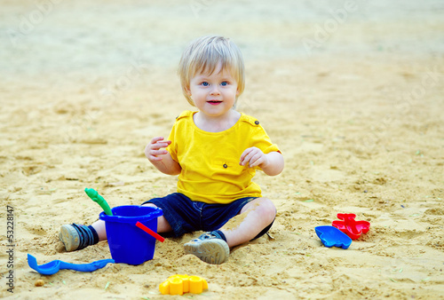 Funny kid playing with his toys in the sandbox