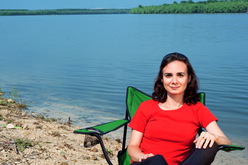 Beautiful young woman relaxing in a chair near the lake