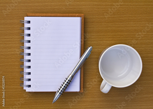 Note book and pen and coffee cup and camera. On the floor of the