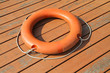 An orange lifebuoy ring on wooden floor