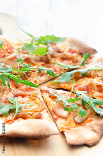 Pizza with tomato, caramelised onion and rocket