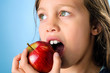 Close up portrait of a young girl eating an apple