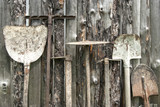 Used farm hand implements on wooden shed wall background