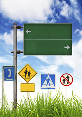 Traffic signs on green grass and blue sky.