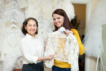 consultant helps to girl chooses  bridal clothes