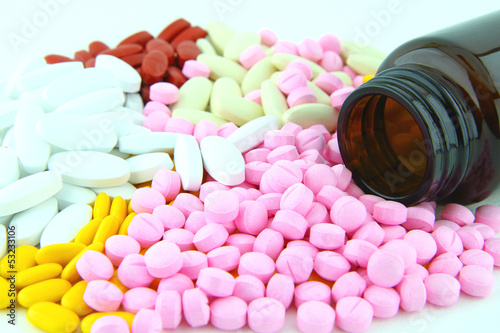 Closeup image of colorful pills and brown bottle