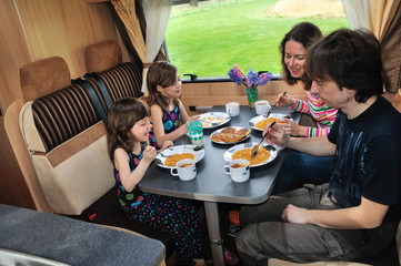 Family eating in RV interior, travel in camper on vacation