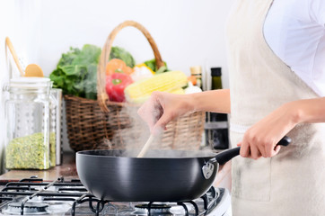 Woman standing by stove cooking and preparing meal
