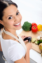 Smiling woman cutting vegetables in the kitchen