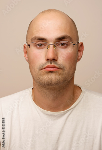 Portrait. Bald man with glasses.