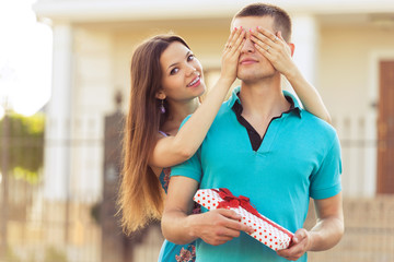 woman covering man's eyes hands