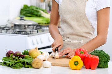 Hands holding knife cutting vegetables in domestic kitchen