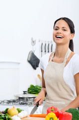 Happy woman enjoying cooking in the kitchen