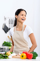 Smiling woman in the kitchen preparing dinner