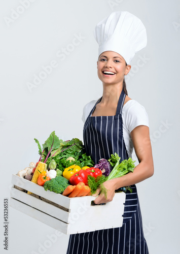 Chef with box full of raw vegetables