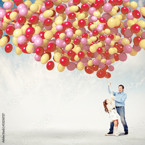 Father and daughter holding balloons