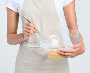 Woman in apron beating eggs in a glass bowl
