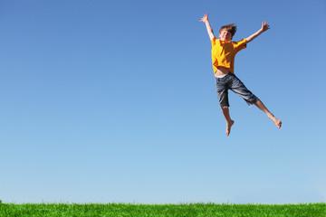 Fröhlicher Junge springt hoch
