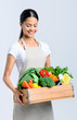 Healthy happy woman with crate of vegetables