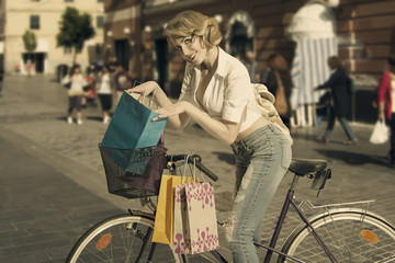 smiling shopping girl on bicycle vintage color