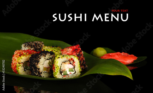 Tasty sushi on green leaf on dark background