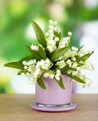 Beautiful lily of the valley in vase on nature background