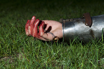 Bloody hand lying on the grass and holding ring
