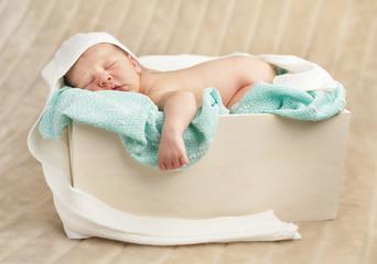 Newborn baby sleeping in a wooden case