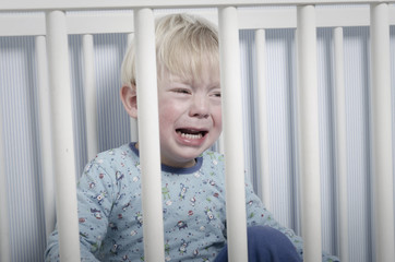 Boy crying in bed does not want to sleep