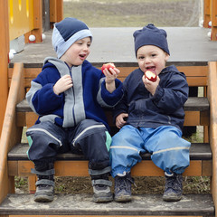 Children eating apples at playground.