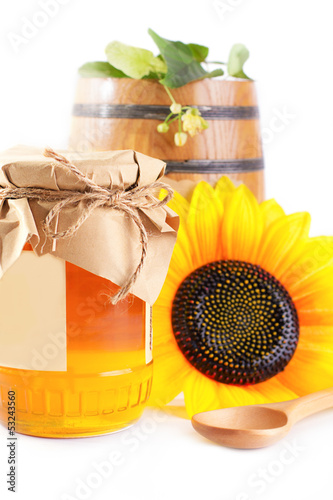 Jar and barrel with honey and flowers