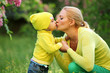 Little boy kissing his mother outdoors