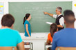 teacher pointing at chalkboard with student standing in front of