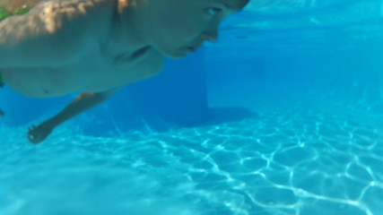 boy swimming underwater in sea or pool