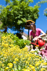 Junge Frau gießt Blumen im Garten