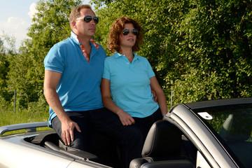 junges Paar am Heck eines Sportwagens