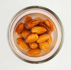 Macro of almonds soaking in water isolated on white