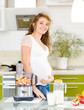 pregnant woman with healthy food in kitchen