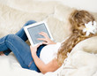 pregnant woman lying down on sofa and reading ebook