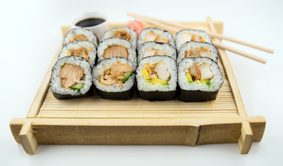 Teriyaki and fried chicken sushi rolls on Japanese bamboo mat